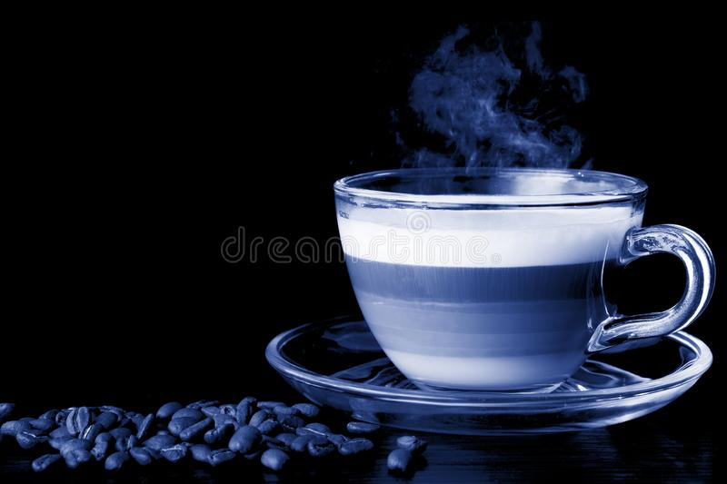Classic blue background. Transparent glass cup hot cappuccino with visible layers of coffee, milk and foam. coffee beans stock photography