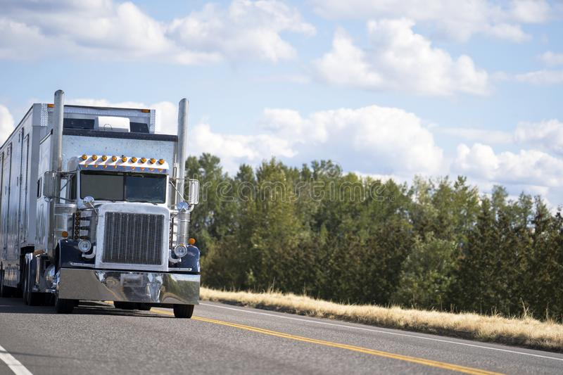 Classic big rig semi truck with reefer semi trailer and refrigerated unit driving with cargo on the road. Classic blue big rig American bonnet semi truck with stock image