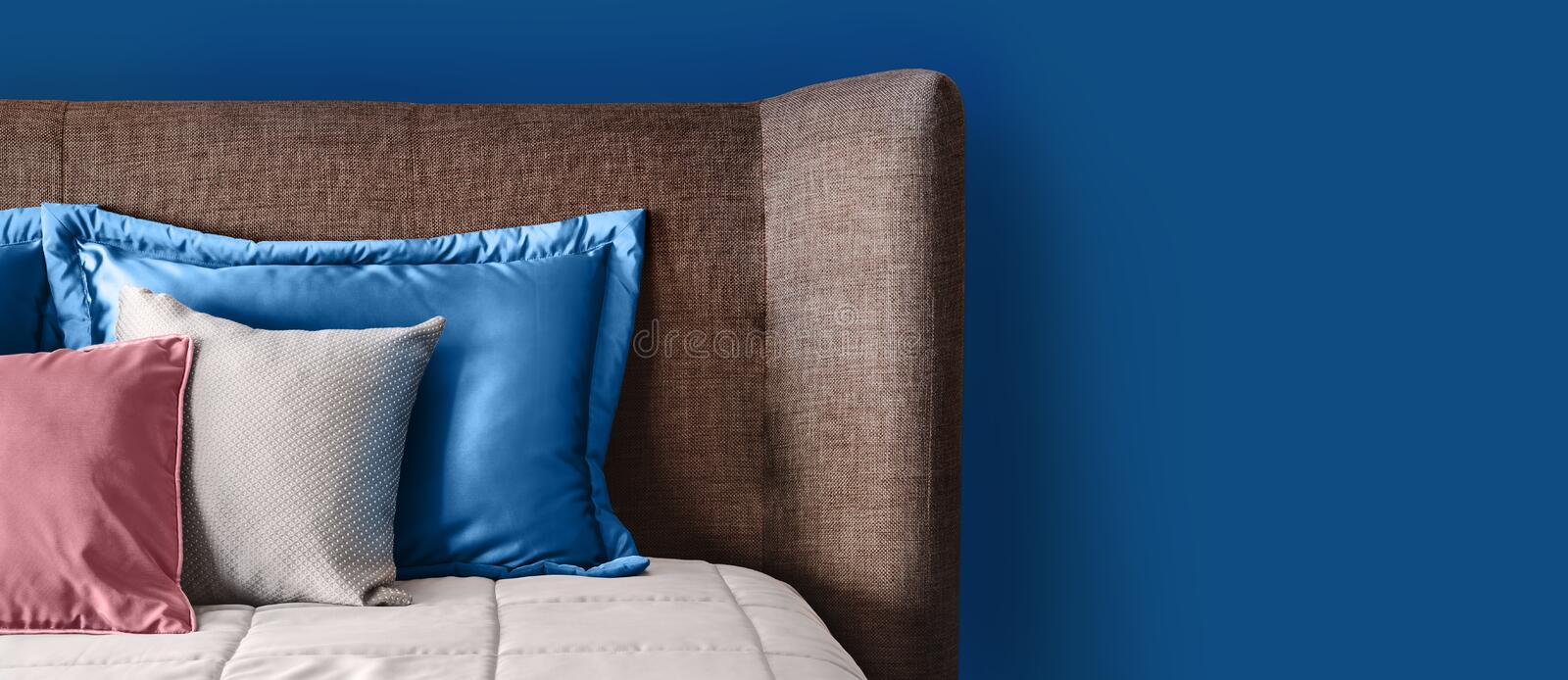 Classic blue color in living interior. Soft Headboard and pillows. Fragment of cozy modern bedroom stock image