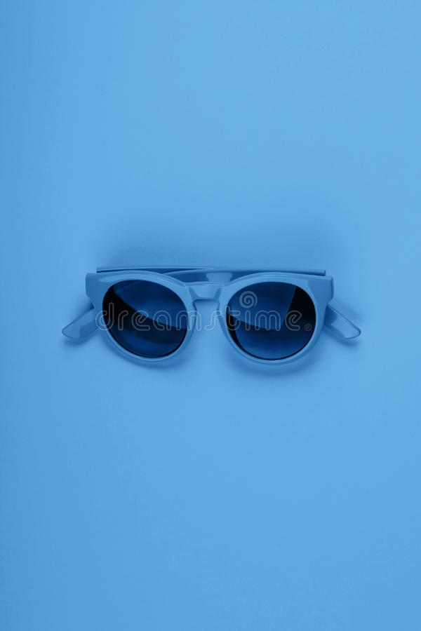 Classic blue sun glasses. Monochrome fashion flat. Classic blue color of 2020 sun glasses. Monochrome minimal fashion flat lay royalty free stock photos