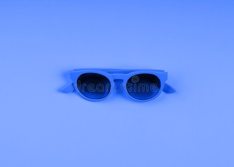 Classic blue sun glasses. Monochrome fashion flat. Classic blue color of 2020 sun glasses. Monochrome minimal fashion flat lay stock photography
