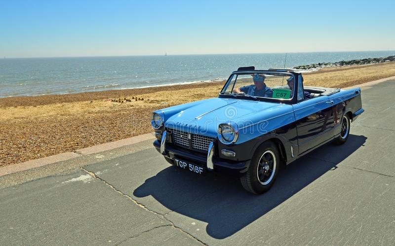 Classic Blue Triumph Herald Convertible Car being driven along Seafront Promenade. stock photo