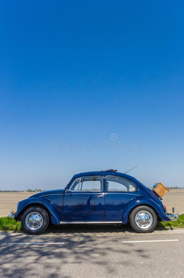 Classic blue Volkswagen beetle on a country road. In The Netherlands royalty free stock photos