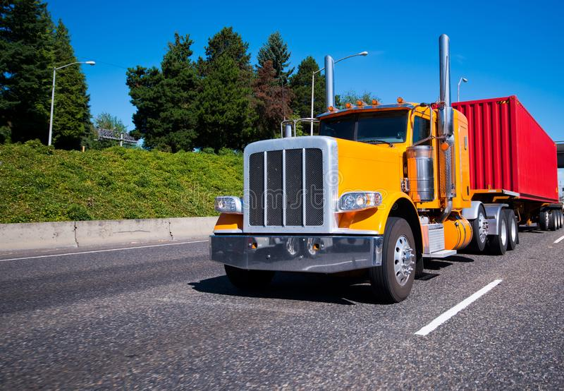 Classic orange big rig semi truck with red container on flat bed stock images