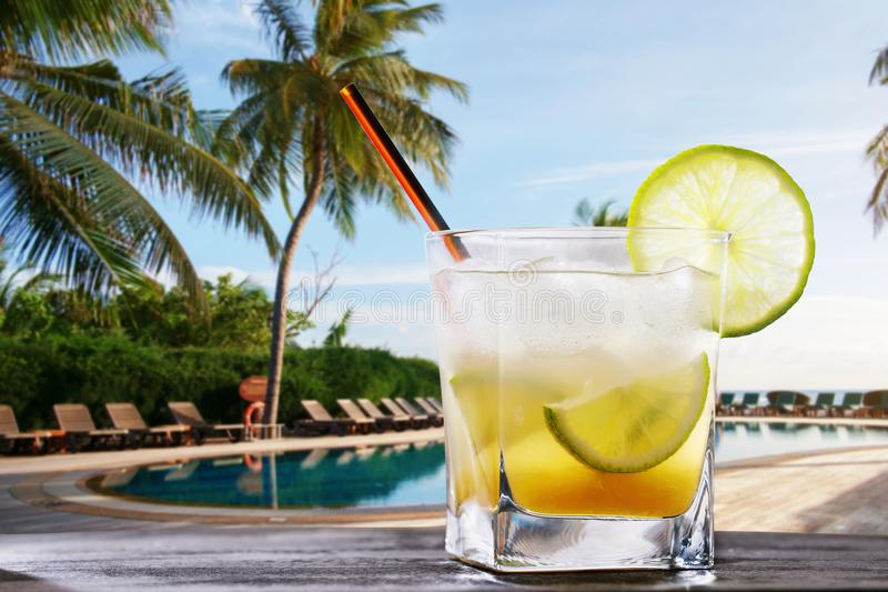 Classic Brazilian cocktail of caipirinha. Freshly prepared alcoholic drink on the background of the pool with space for text royalty free stock image