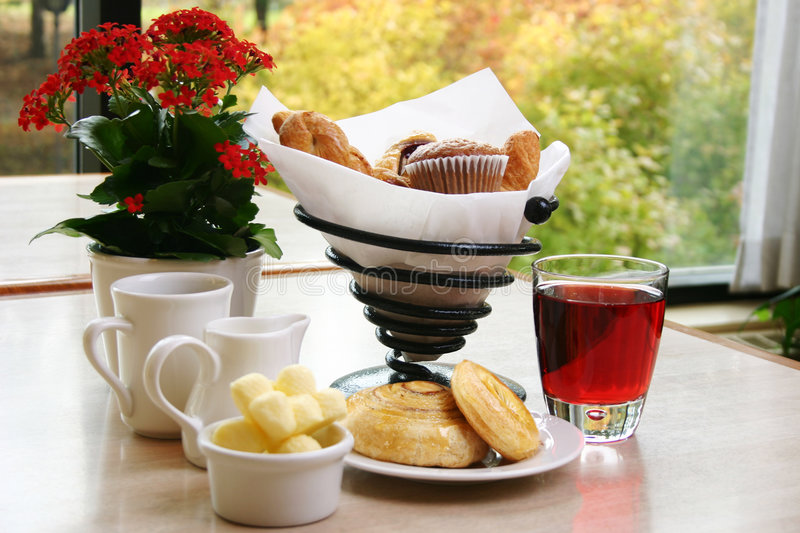 Classic Breakfast. Breakfast of muffins, croissants, danish pastries, cranberry juice and coffee royalty free stock photography