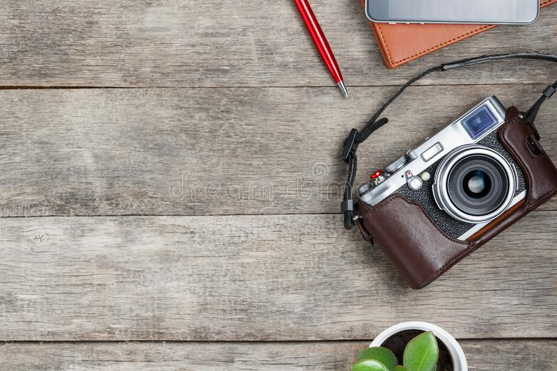 Classic camera on a gray wooden background, with a brown notepad, a red pen, a telephone and green growth. Concept list for a. Travel photographer. Free place stock photography