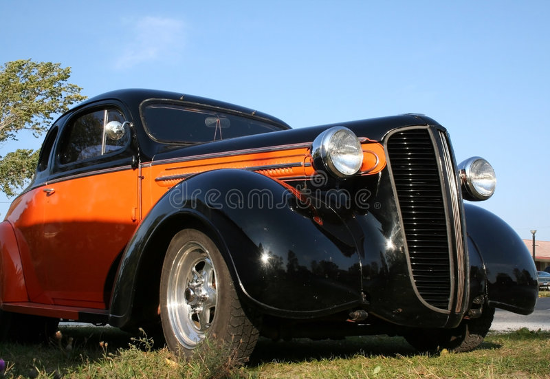 Classic car. Orange and black coloured classic car royalty free stock images