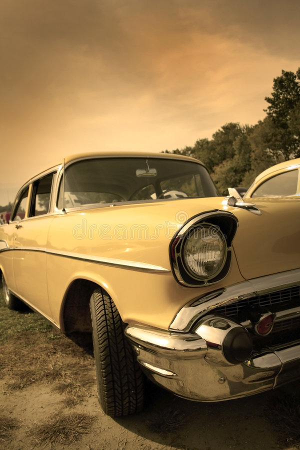 Classic car. Head lamp of yellow classic car in sepia color tone royalty free stock photo