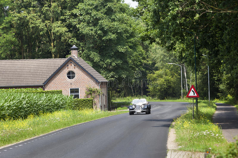 Classic car on a country road in the Netherlands royalty free stock photography