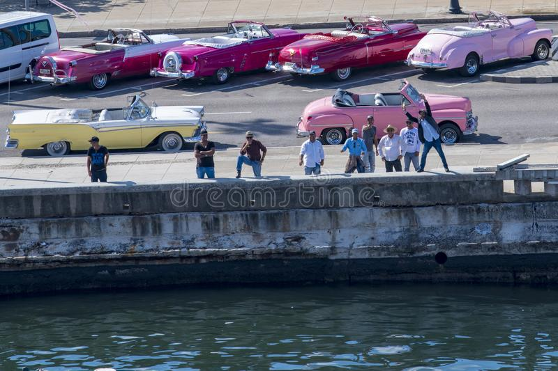 Classic car driver welcome cruise tourists in Havana, Cuba royalty free stock photography