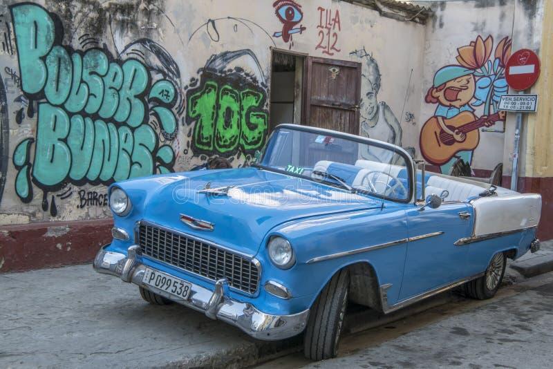 Classic car in front of graffiti, Cuba stock images