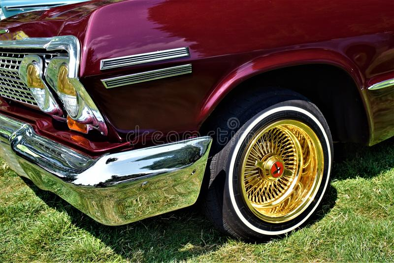 Classic Car with golden tire rims and chrome. This classic car was brillant from the shine with its golden tire and chrome royalty free stock photography