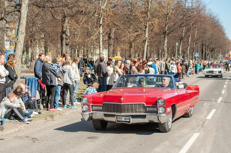 Classic car parade on May Day celebrates spring in Sweden. Norrkoping, Sweden - May 1, 2013: Spectators enjoy a 1968 Cadillac at the classic car parade stock photos