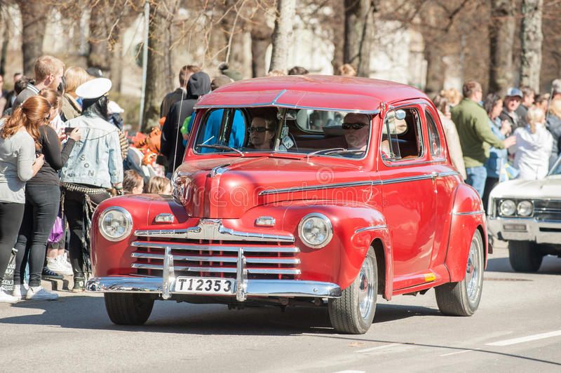 Classic car parade on May Day celebrates spring in Sweden. Norrkoping, Sweden - May 1, 2013: Spectators enjoy at the classic car parade celebrating spring on May stock image