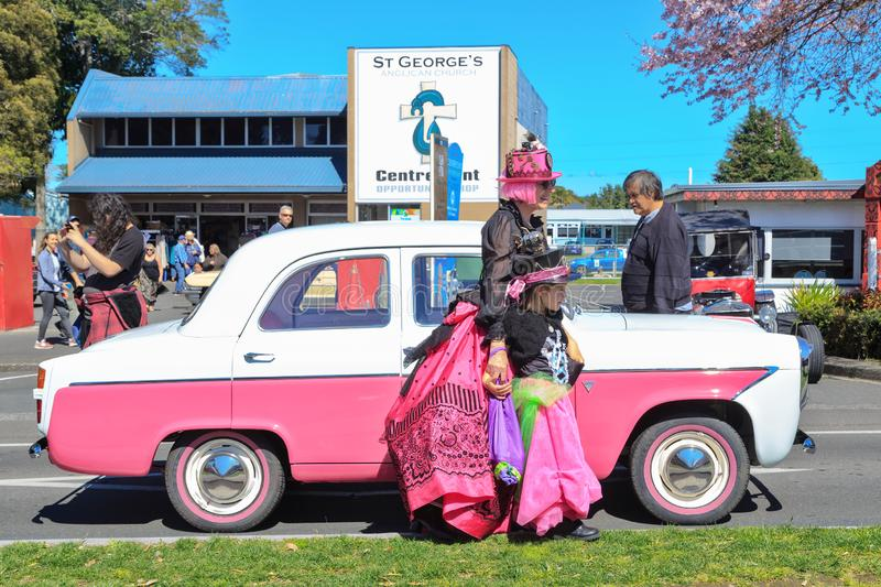 Classic car, woman, and girl, all in bright pink royalty free stock photography