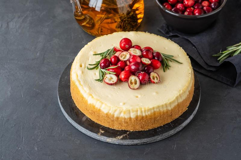 Classic cheesecake with cranberries and rosemary on a dark background. Winter version of cheesecake. Christmas stock image