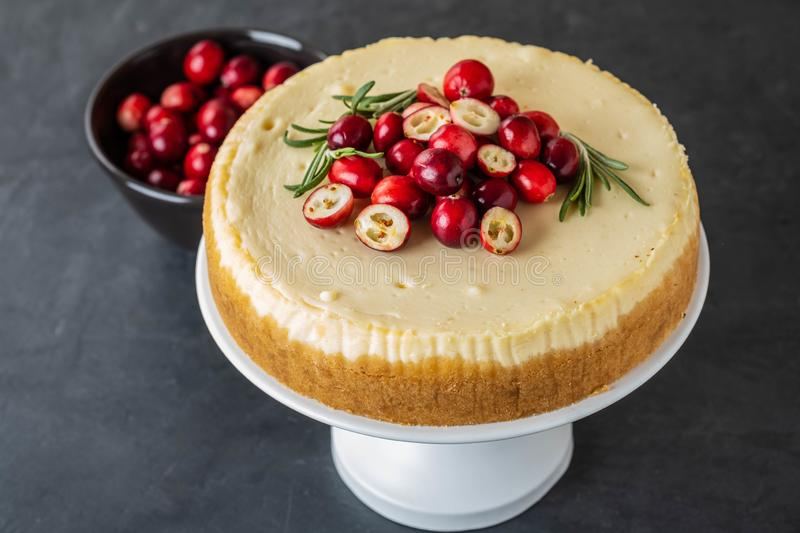 Classic cheesecake with cranberries and rosemary on a dark background. Winter version of cheesecake. Christmas stock images
