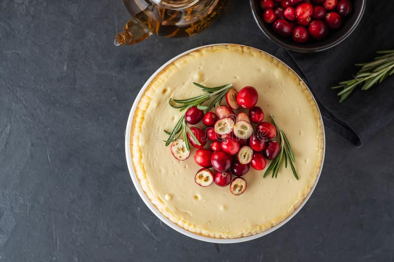 Classic cheesecake with cranberries and rosemary on a dark background. Winter version of cheesecake. Christmas royalty free stock image