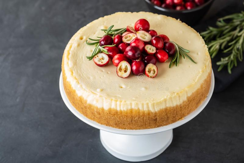 Classic cheesecake with cranberries and rosemary on a dark background. Winter version of cheesecake. Christmas royalty free stock images