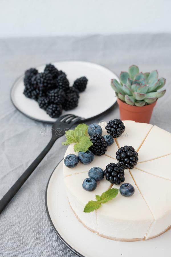 A classic cheesecake decorated with blueberries and blackberries stock photo