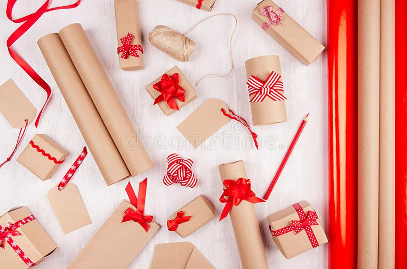 Classic christmas design of decoration - gift boxes of kraft paper with bright red bows and ribbons on soft white wood table, top. stock images