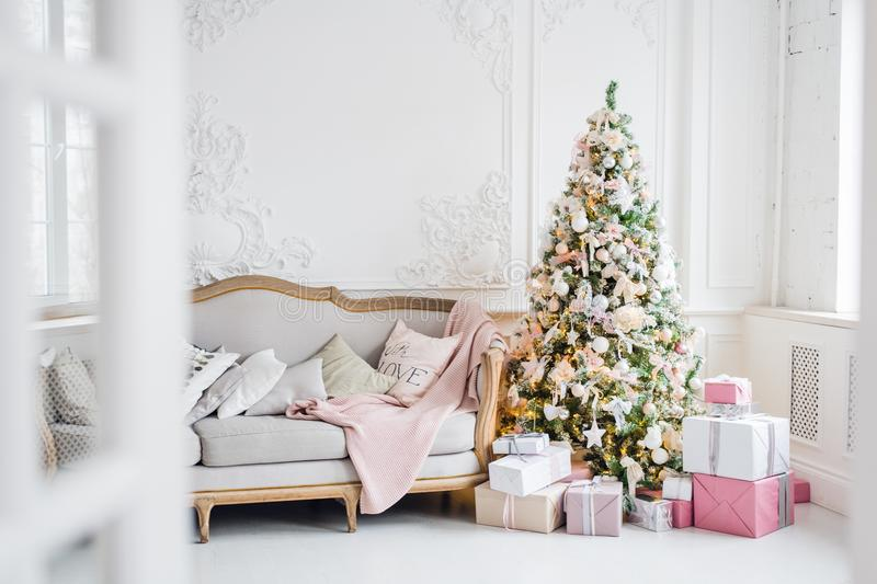 Classic Christmas light interior in white and pink tones with a couch, tree and molding in the Baroque style and stock photo