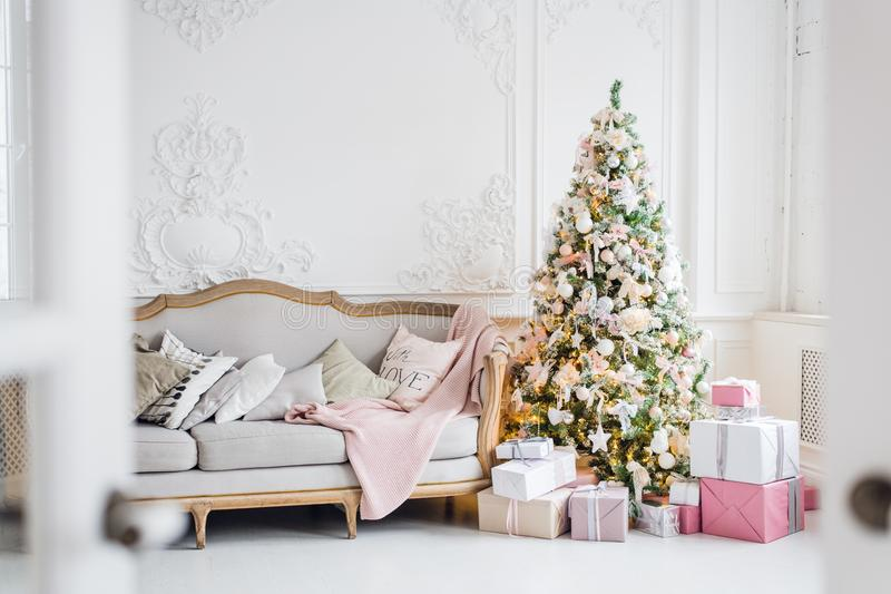 Classic Christmas light interior in white and pink tones with a couch, tree and molding in the Baroque style and stock images