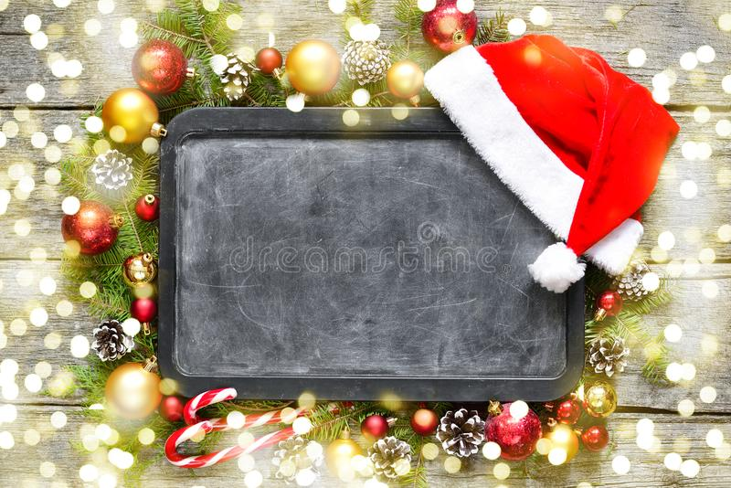 Classic christmas and new year composition chalk board, balls, toys, candy, fir branches on vintage wooden background stock photography