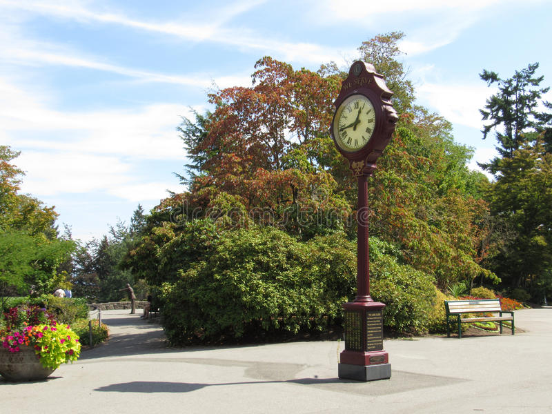 A Classic Clock at Queen Elizabeth Park, Vancouver, Canada. A statue bowing in the background stock image