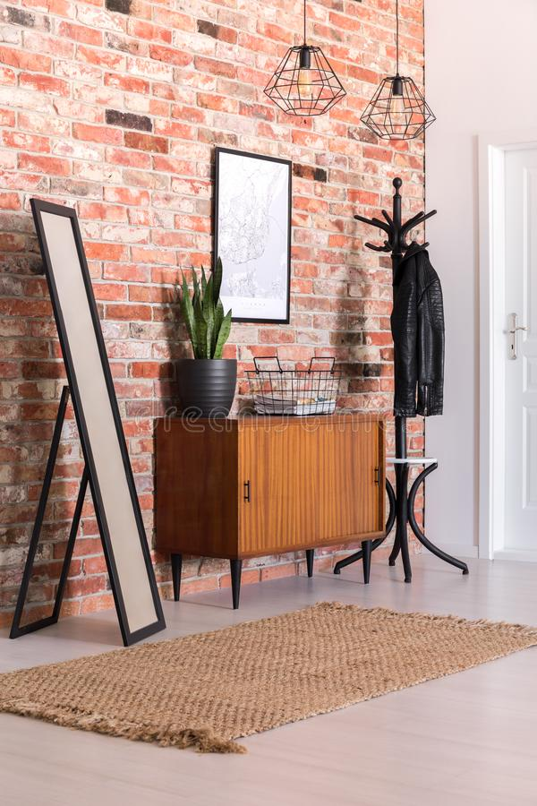 Classic corridor with brick wall, clothes hanger, cupboard, carpet and mirror. Real photo royalty free stock photos