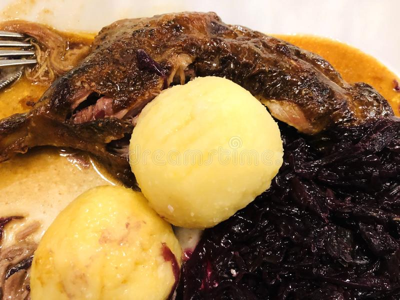 Classic and crispy roasted goose with red cabbage and dumplings. St. Martin`s goose royalty free stock photography