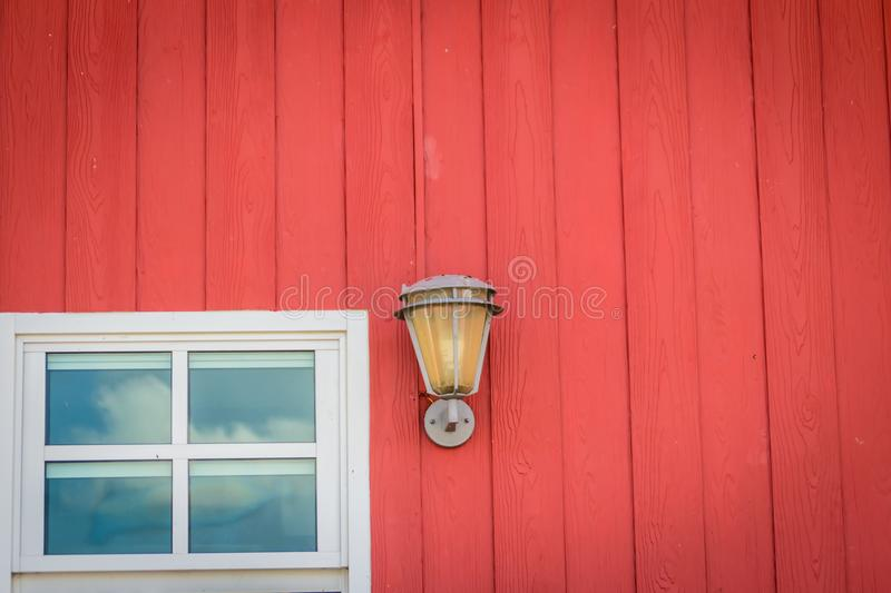 Classic design wall decoration with window glass and lighting lamp on the painted red wooden wall. Vintage metal lantern on red wa stock images