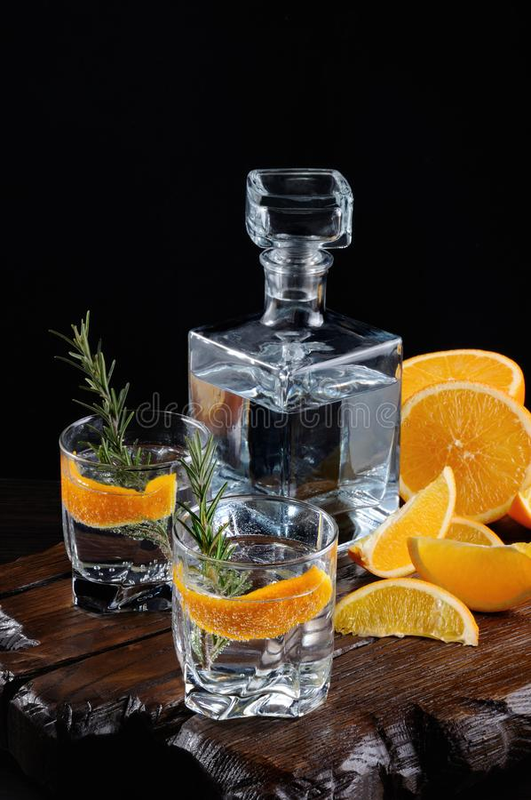 Classic Dry Gin with tonic and orange zest. Cocktail classic Dry Gin with tonic and orange zest with a sprig of rosemary on a wooden board with slices juicy royalty free stock photography