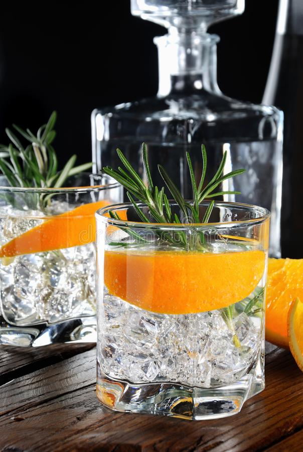 Classic Dry Gin with tonic and orange zest. Cocktail classic Dry Gin with tonic and orange zest with a sprig of rosemary on a wooden board with slices juicy stock image