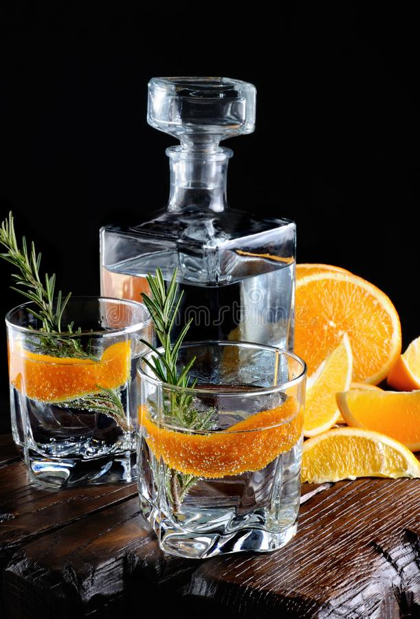Classic Dry Gin with tonic and orange zest. Cocktail classic Dry Gin with tonic and orange zest with a sprig of rosemary on a wooden board with slices juicy stock images