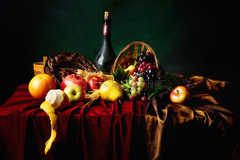 Classic Dutch still life with dusty bottle of wine and fruits on a dark green background, horizontal royalty free stock photos