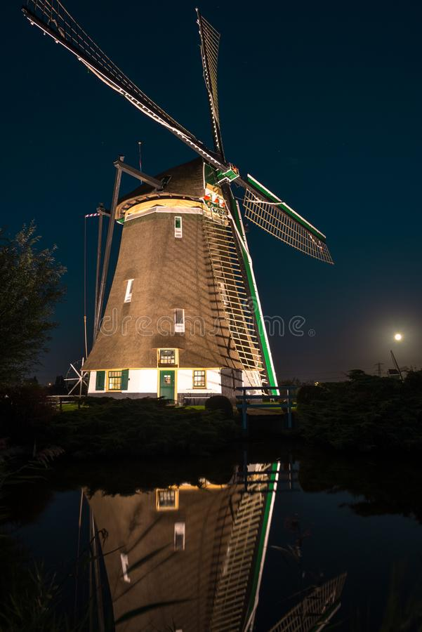 Classic dutch windmill is illuminated at night with beautiful reflections in the water royalty free stock image
