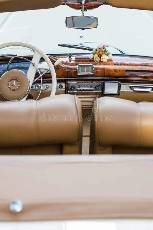 Classic European Mercedes oldtimer interior. The interior of the Mercedes oldtimer in a beige and white color, covered with leather and wood, Pforzheim, Germany royalty free stock photos