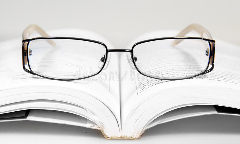 Classic eyeglasses on a text book royalty free stock image