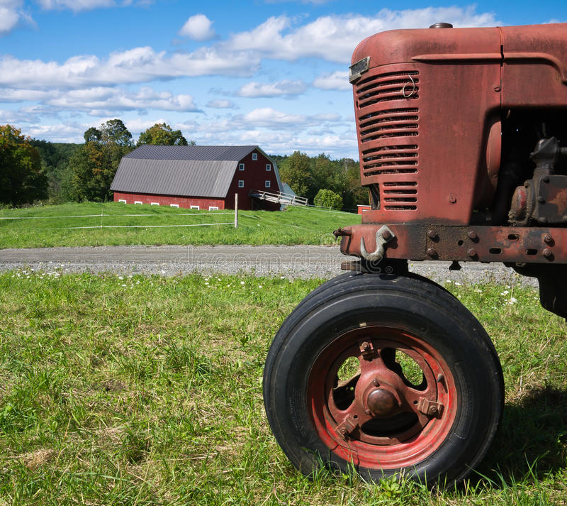 Classic Farming Scene Red Tractor and Barn. A New England family farm landscape showing a red tractor, red dairy barn and freshly mowed green fields. Etna, New stock photos