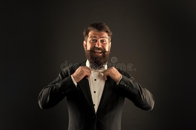 Classic and fashionable. Happy groom fix fashionable bow tie. Bearded man in fashionable prom style. Fashionable look of. Vogue model. Prom and wedding attire stock image