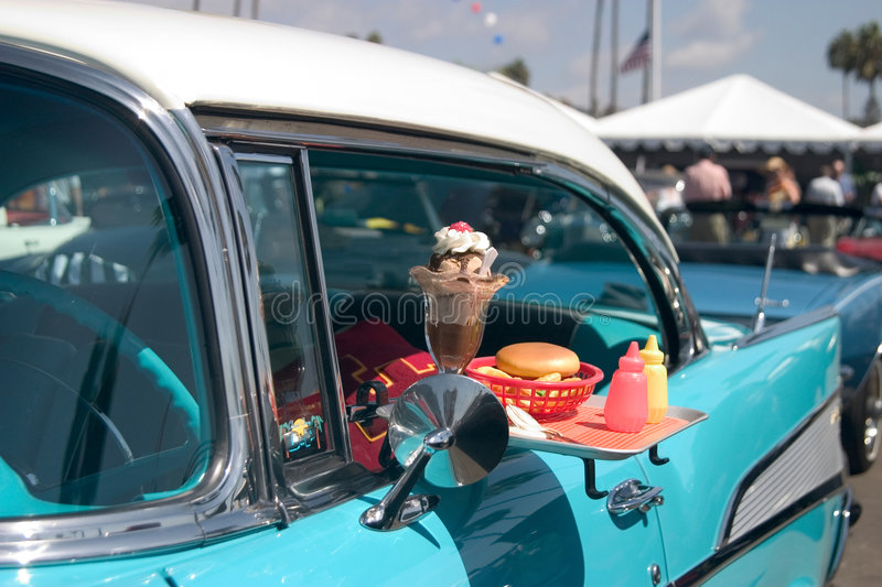 Classic Fast Food. Classic car with food tray attached to the driver's window stock photo