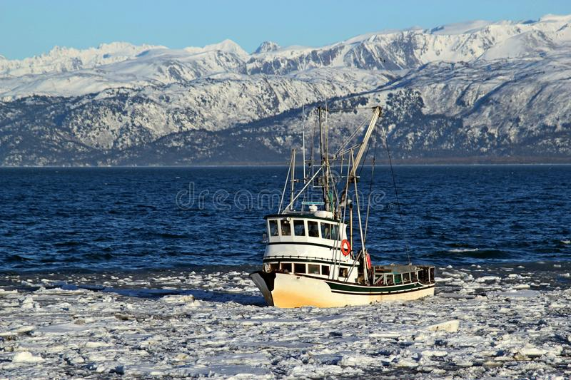 Classic fishing boat in an icy bay stock images