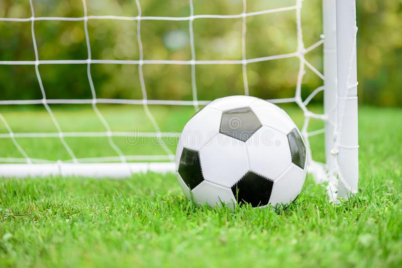 Classic football soccer ball on green grass ground in front of white goal with net. Children soccer goal and generic white and black ball on grass royalty free stock image