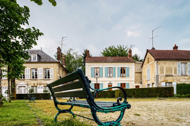 Classic french bench on the street of a little village royalty free stock photo