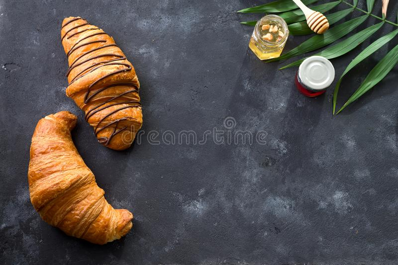 Freshly baked croissant decorated with chocolate sauce, jar with jams and palm leave isolated on a gray slate background stock photography