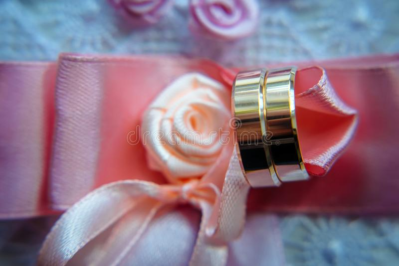 Classic gold wedding rings on pink ribbons, close-up, selective focus. Vintage photography of the wedding day.  stock image