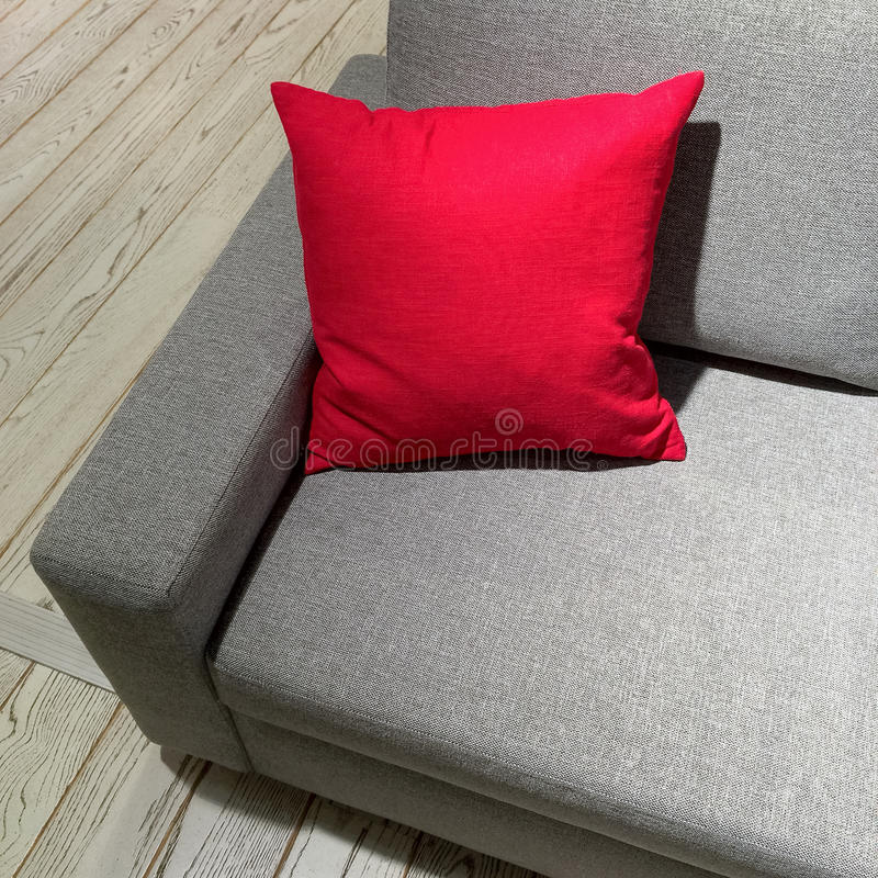 Classic gray sofa with vibrant red cushion. Modern furniture stock photos