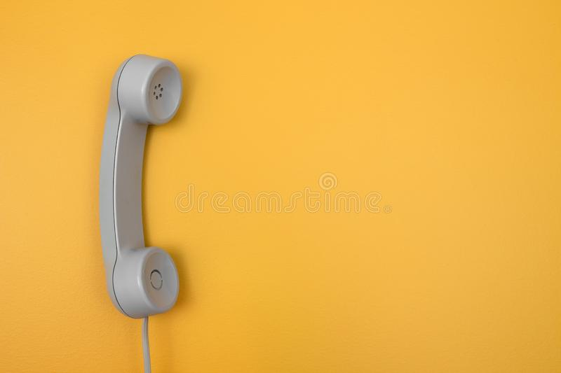 Classic telephone receiver on bright yellow background royalty free stock image